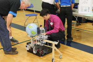 James Xue (right) of Canton, Michigan, answers a question from WRO Judge Fred Brauchler about his team's concept for a robot system that would collect solar energy while in orbit and then deliver the converted energy to the Earth's surface.